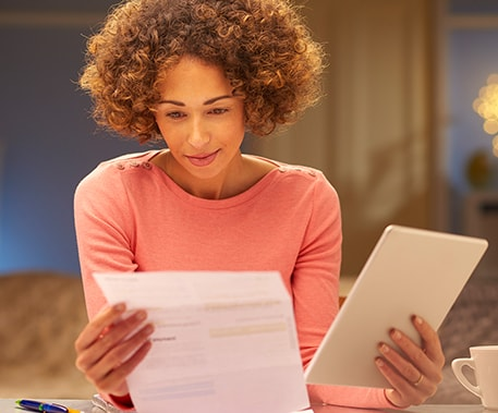 young woman with an iPad is looking at a bill