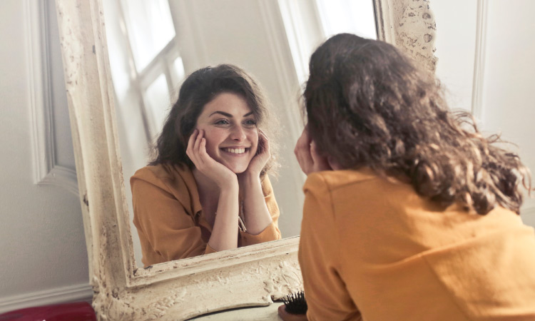 Brunette young woman wearing yellow blouse looks in the mirror and smiles excitedly after her dental cleaning