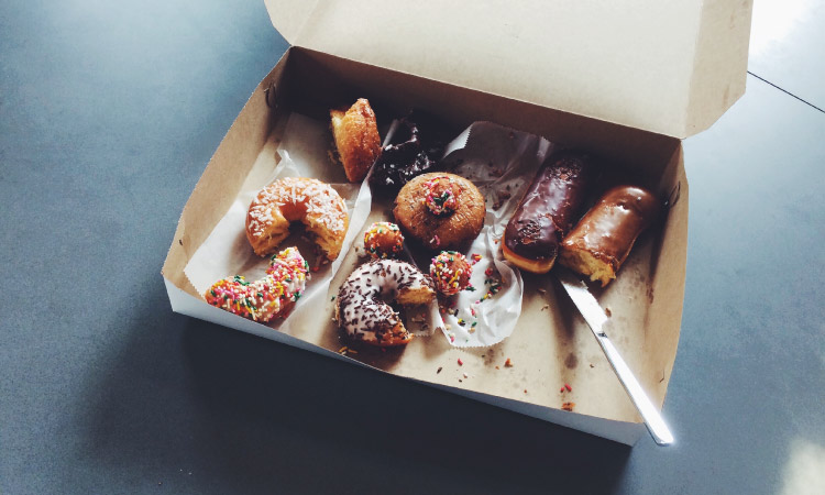 An open cardboard box of half-eaten donuts with chocolate glaze and sprinkles that can cause cavities