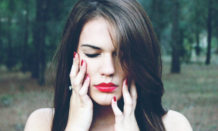 Closeup of brunette woman with red lipstick and fingernails touching her cheeks due to tooth sensitivity and pain